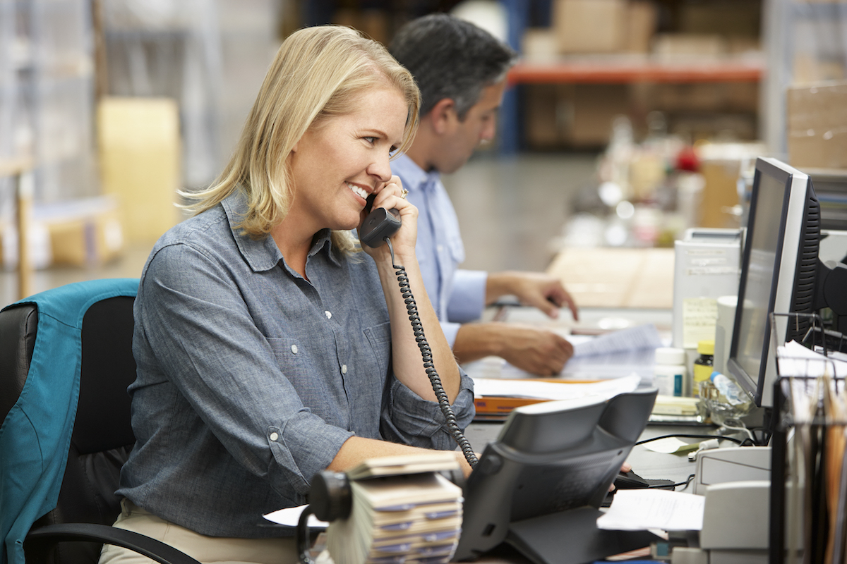Businesswoman Working At Desk In Warehouse